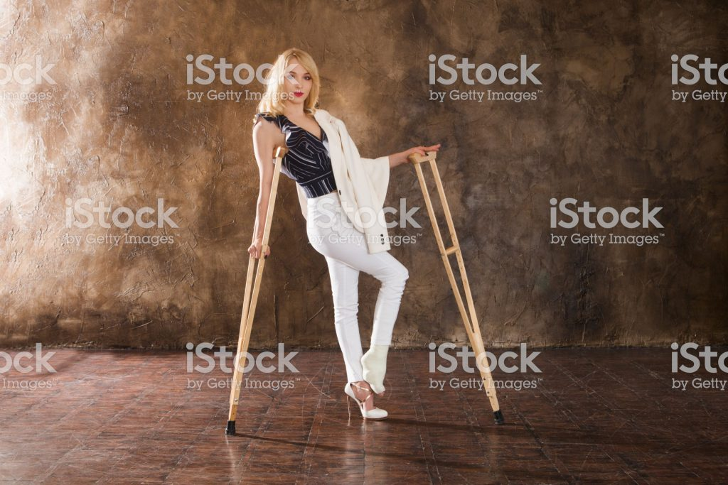 Young elegant woman with crutch and broken leg against the background of a wall